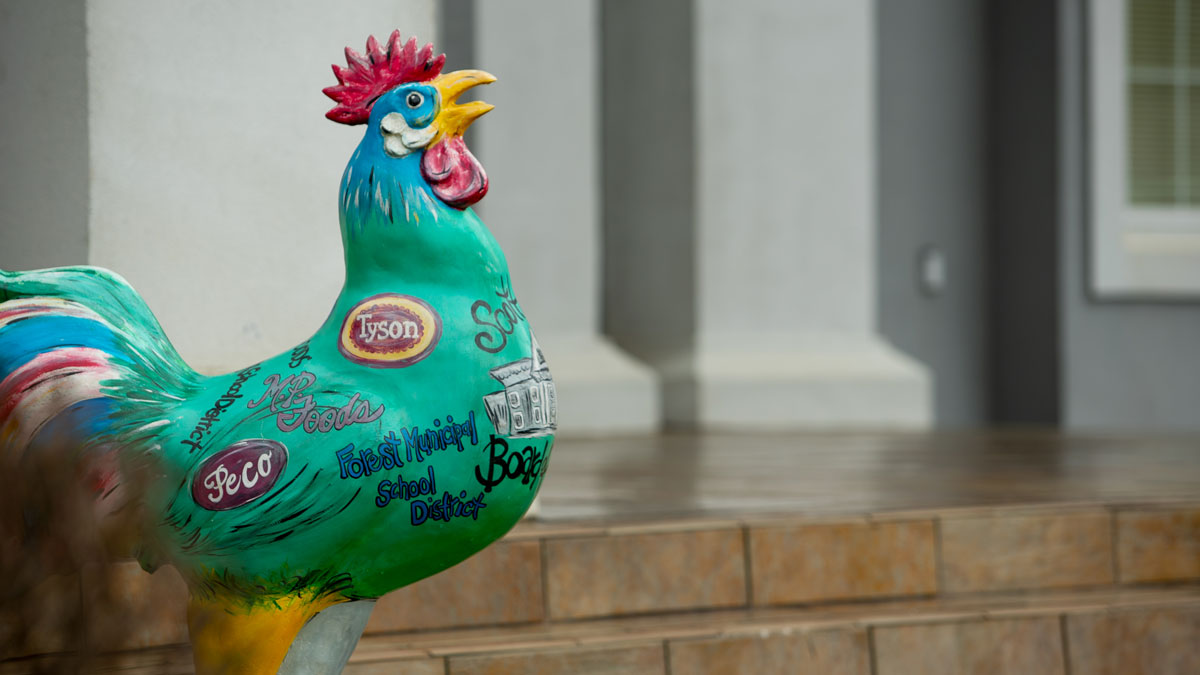 A brightly painted chicken on the steps of the a courthouse in Forest, Mississippi, celebrates various chicken plants from around the area.