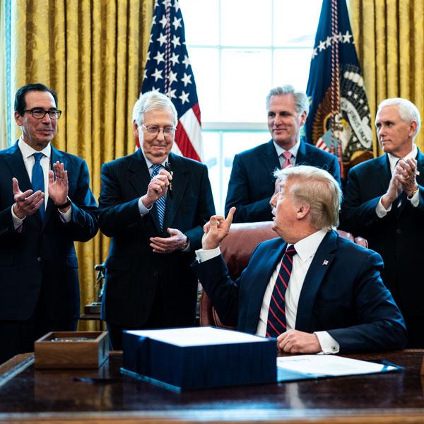 President Donald Trump signs the $2 trillion coronavirus stimulus bill last week in the Oval Office.