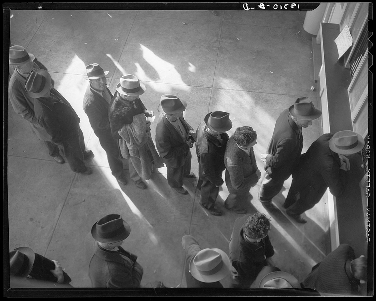 A group of men wait in line for unemployment benefits in the early 20th century.