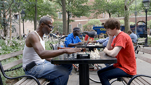 """A still from """"The Prison in Twelve Landscapes"""" shows Nahshon Thomas, a formerly incarcerated man who teaches chess in Washington Square Park in New York City, playing at a table."""